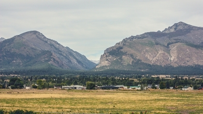 Two sturdy mountain peaks come together, at their base lies one of the many scenic and safe communities that permeate the Ravalli County in Montana.