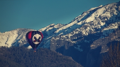 Fortified mountains brace for the passing of a red and white hot air balloon.